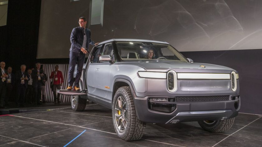 Rivian Chief Executive R.J. Scaringe perches on his company's R1T electric truck during the vehicle's debut at the Los Angeles Auto Show in November.