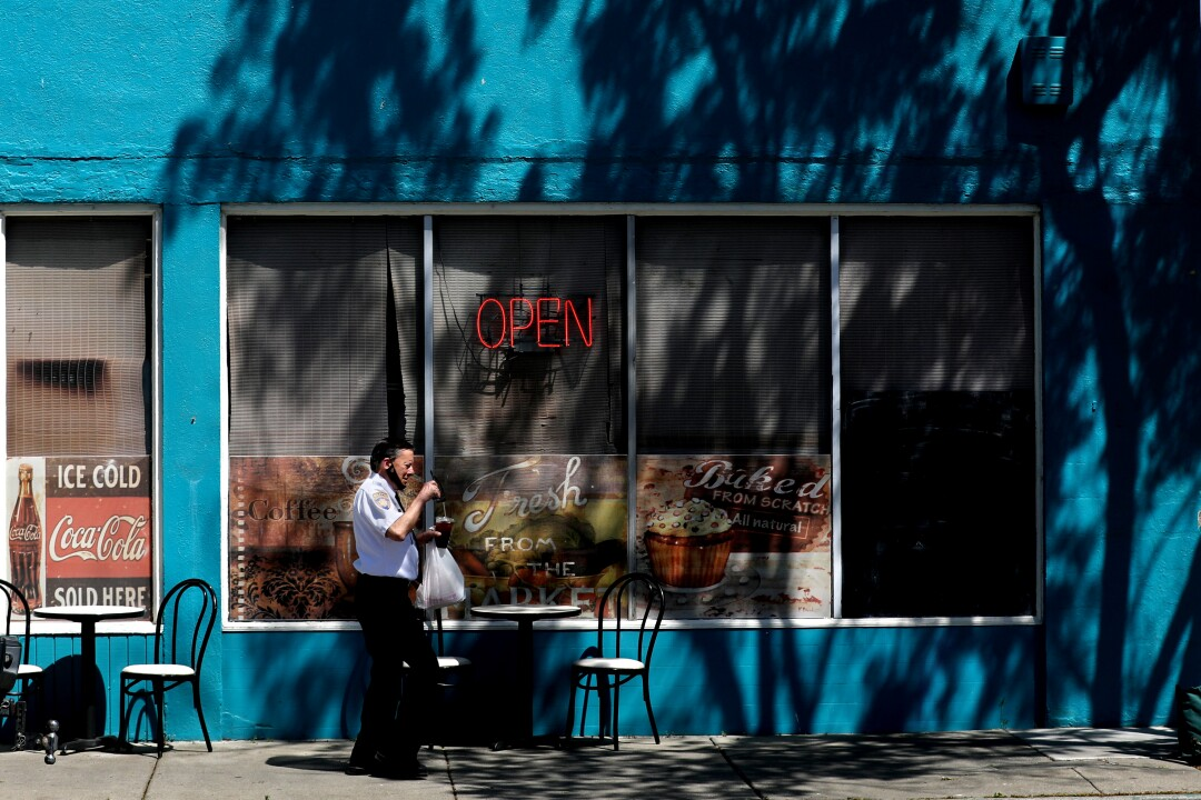 A customer leaves with a take-out order at Courthouse Cafe in Marysville.