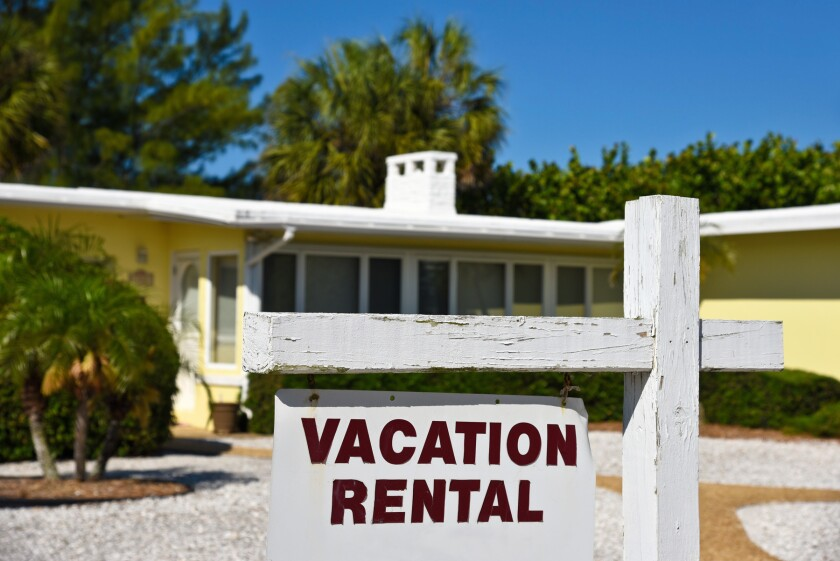 A Vacation Rental Sign in front of a yellow one story home on the beach.