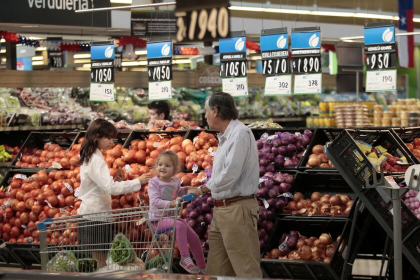 In this Sept. 2, 2015, photo, a man and his family shop in a Wal-Mart Express de LIDER in Santiago, Chile. Chile is a bright spot in Wal-Mart's international business, which has become ever more important as growth in the U.S. has slowed. (AP Photo/Luis Hidalgo)