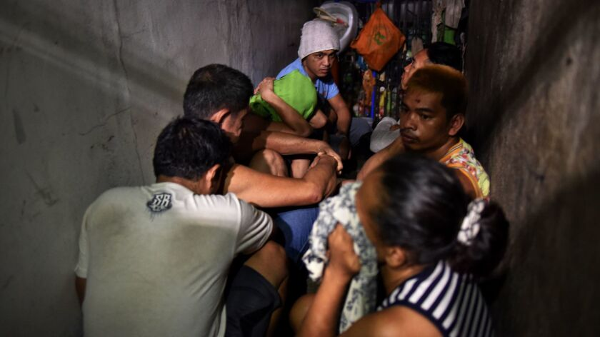 Drug suspects are detained at a secret cell behind a wooden cabinet in Manila.