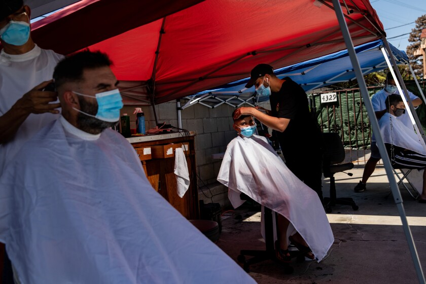 Nader Salameh, left, and his son Gavyn from Lawndale, get their hair cut.