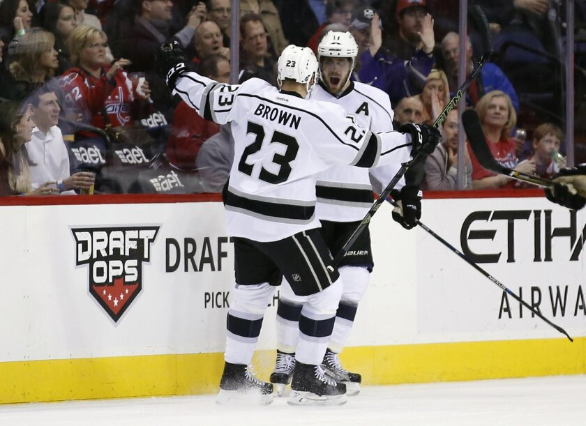 Los Angeles Kings right wing Dustin Brown (23) and center Anze Kopitar (11), from Slovenia, celebrate a goal by Kopitar in the first period of an NHL hockey game against the Washington Capitals, Tuesday, Feb. 16, 2016, in Washington. (AP Photo/Alex Brandon)