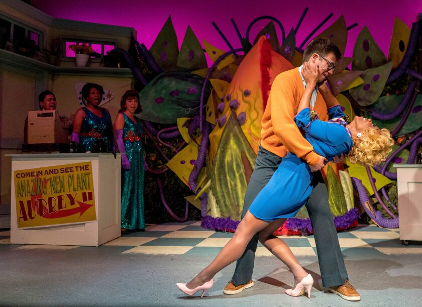 """Sittichai Chaiyahat as Seymour and Cashae Monya as Audrey in New Village Arts' """"Little Shop of Horrors."""" At back left are the Doo-Wop ensemble played by Chris Bona, far left, Patricia Jewel and Natasha Baenisch."""