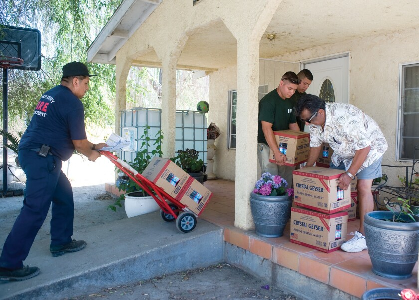 Volunteers deliver cases of water to homes in East Porterville on Friday. Hundreds of people whose wells have gone dry due to drought received an emergency allotment of bottled water from Tulare County officials.