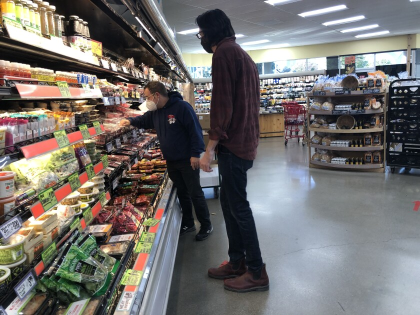 A grocery worker helps a visually impaired shopper.