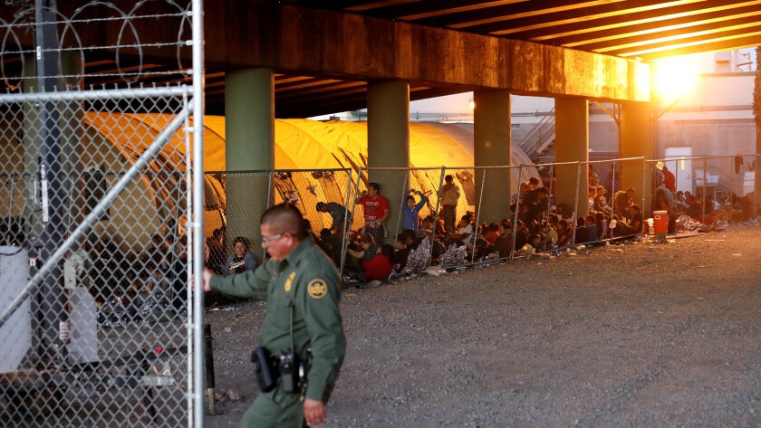 Hundreds of migrants seeking asylum are held in a temporary transition area under the Paso Del Norte bridge in El Paso, Texas.