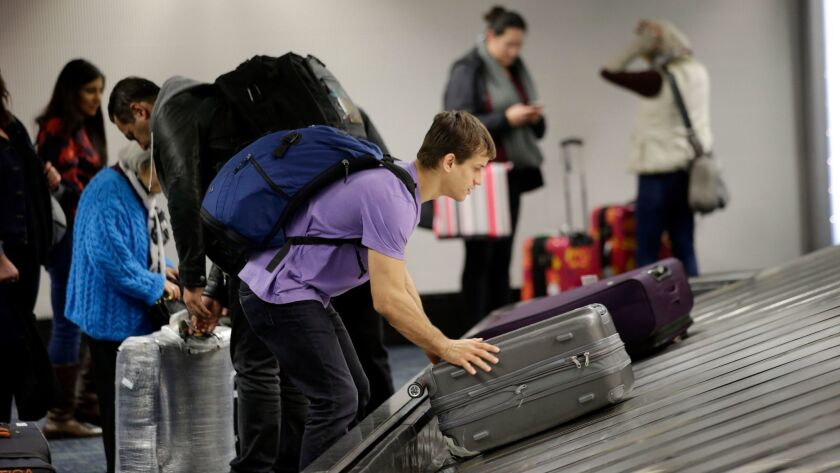 A traveler gathers his luggage at the San Francisco International Airport. American Airlines has launched a program that alerts travelers when their bags don't arrive at the same airport.