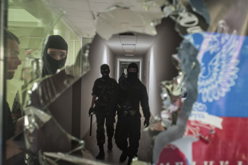 Pro-Russia separatists, as seen in this April 26 photo occupying the Mariupol city administration building, have been driven out of the eastern Ukrainian port by police patrols bolstered by steelworkers from oligarch Rinat Akhmetov's industrial empire.