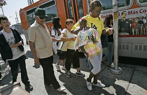 Passengers are ready to board a bus at the intersection of Vernon and Central avenues in South Los Angeles, a gang-infested area where five children and three adults were shot a month ago. Residents say the unusual thing about the shooting is that the outside world noticed.