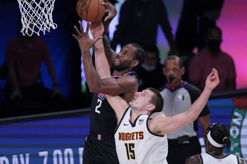 Kawhi Leonard grabs a rebound over Denver Nuggets center Nikola Jokic.