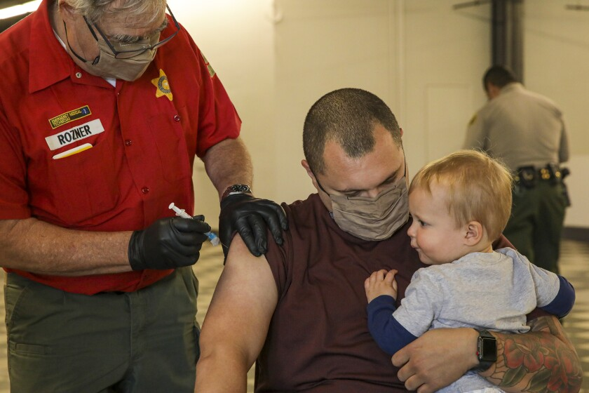 A man holding a baby receives a COVID-19 vaccination.