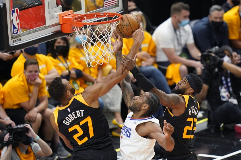 Utah Jazz's Rudy Gobert (27) and Royce O'Neale (23) defend against Los Angeles Clippers forward Kawhi Leonard, center, during the first half of Game 1 of a second-round NBA basketball playoff series Tuesday, June 8, 2021, in Salt Lake City. (AP Photo/Rick Bowmer)