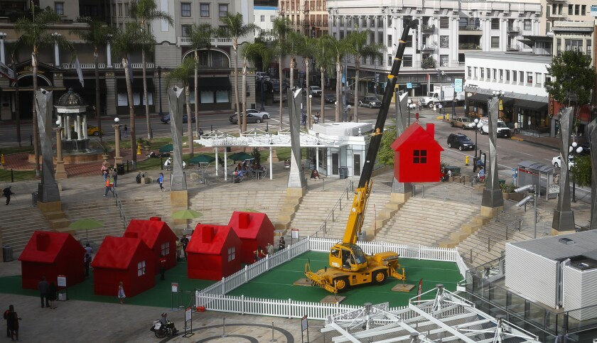 At Horton Plaza Park the art project Model Home created and designed by Mimi Lien is hoisted up sixt