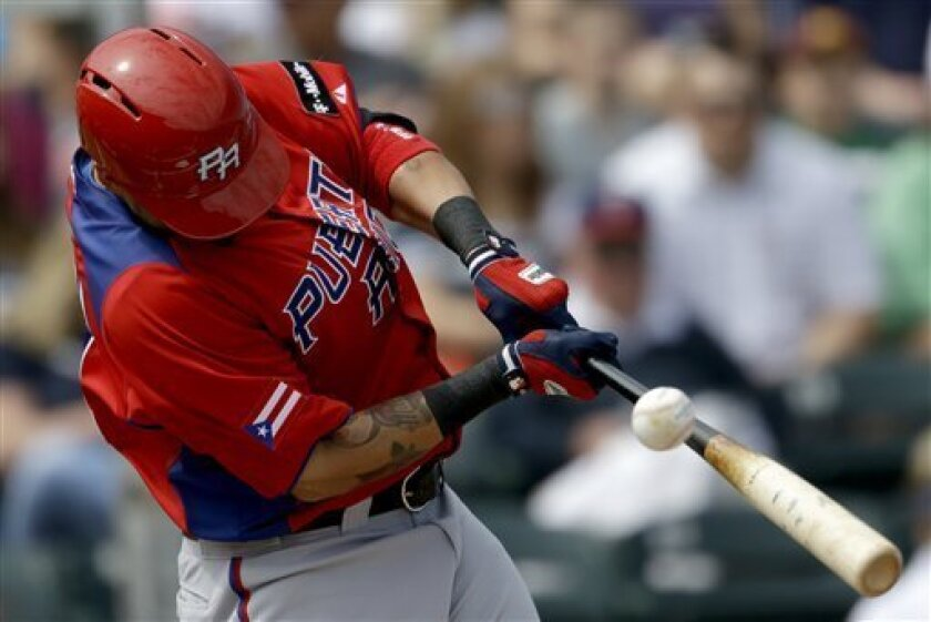 Puerto Rico's Yadier Molina hits a line drive caught by Minnesota Twins first baseman Jeff Clement for an out in the first inning of an exhibition baseball game, Wednesday, March 6, 2013, in Fort Myers, Fla. (AP Photo/David Goldman)