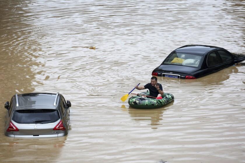 En esta imagen publicada por la agencia de noticias Xinhua, un hombre rema en un bote hinchable junto a varios autos sumergidos durante una inundación en el condado de Rongshui, región autónoma de Guangxi Zhuang, en el sur de China, el sábado 11 de julio de 2020. (Long Linzhi/Xinhua via AP)