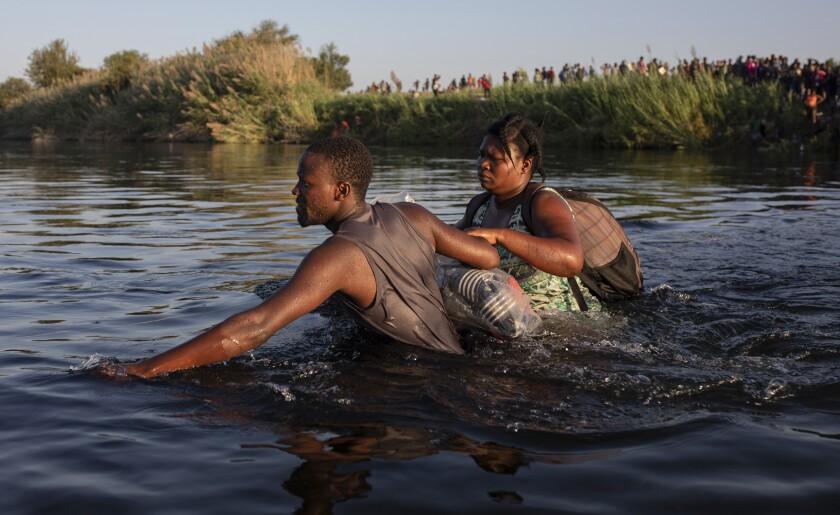 Agentes estadounidenses de Aduanas y Protección de Fronteras intentan contener a migrantes que cruzan el Río Bravo