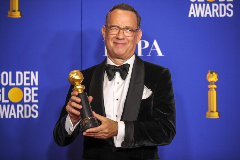 Tom Hanks smiling and holding a Golden Globe award.