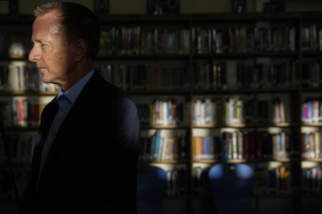 Austin Beutner stands in front of bookshelves.