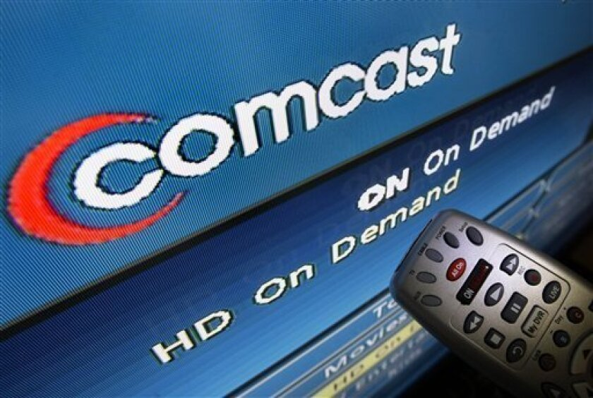 FILE - In this Aug. 6, 2009 file photo, the Comcast logo is displayed on a TV set in North Andover, Mass. Comcast said Thursday Dec. 3, 2009 it will put up $6.5 billion in cash and $7.25 billion in assets to buy 51 percent of NBC Universal from General Electric Co. That means the biggest U.S. cable TV provider would control the NBC and Telemundo networks, about two dozen cable channels and the Universal movie studio and theme parks. (AP Photo/Elise Amendola, File)