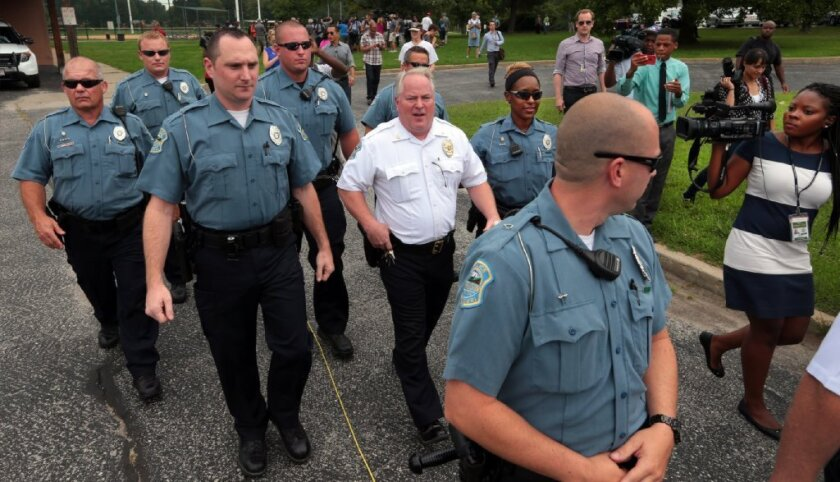 Ferguson Police Chief Tom Jackson, center, leaves a news conference in Forestwood Park on Friday, Aug. 15, 2014.