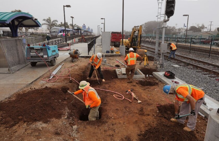 Workers prepare for concrete to be poured Thursday at the Oceanside Transit Center as part of a $24 million improvement project. At upper left a Sprinter train is about the leave the station for Escondido.