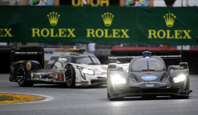 Jordan Taylor, front, leads Christian Fittipaldi (5) through the east horseshoe turn in the IMSA 24-hour auto race at Daytona International Speedway on Sunday.