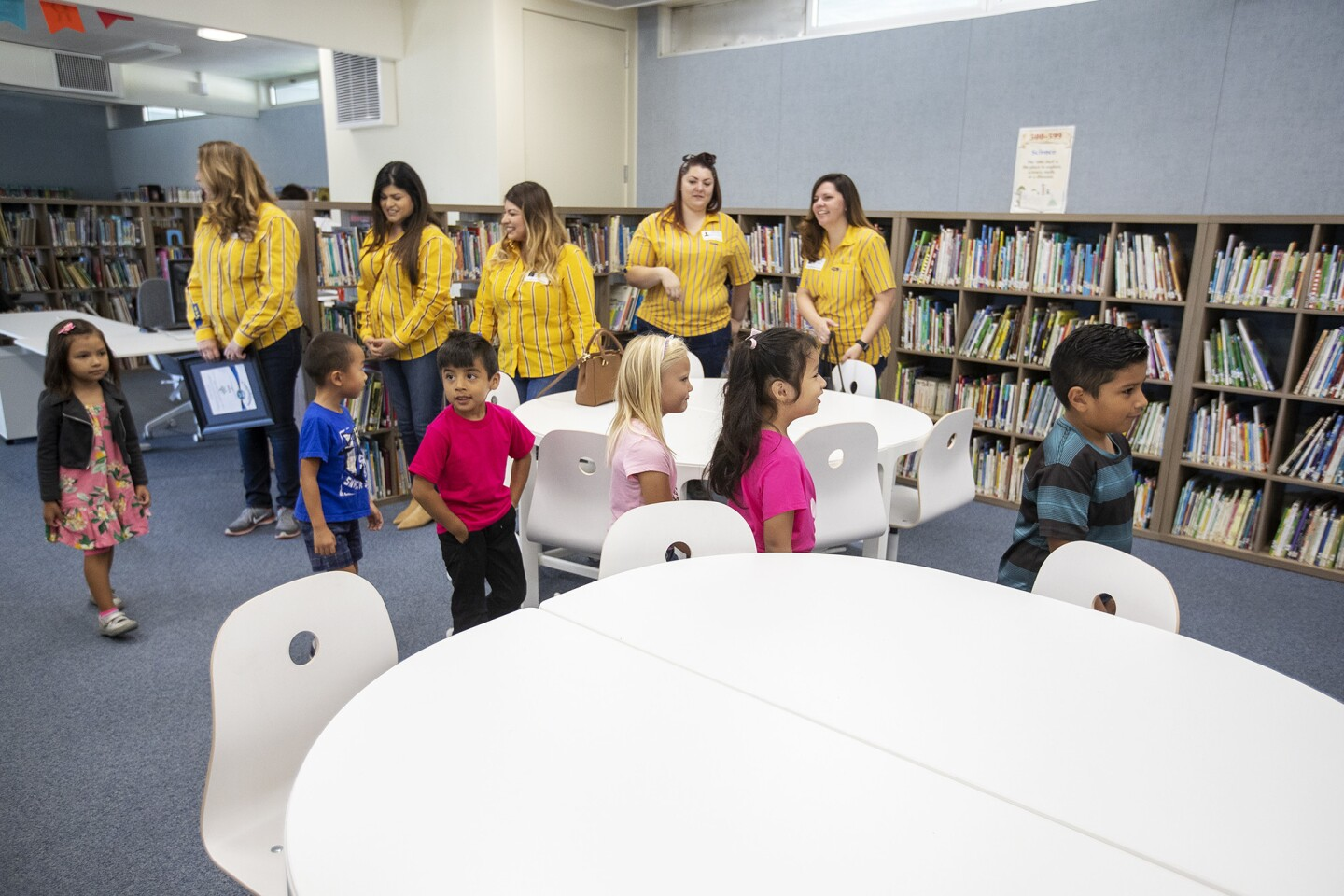 Representatives of IKEA watch as students check out the newly revamped library at Paularino Elementary School in Costa Mesa on Friday. IKEA donated furnishings for a complete remodel.