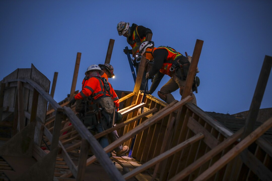 Workers build wooden framework for an arch