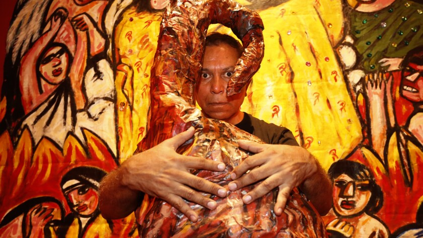 """Gronk holds a piece titled, """"Brain Flame, """" against a backdrop of his painting, """"Cheap Gems."""""""
