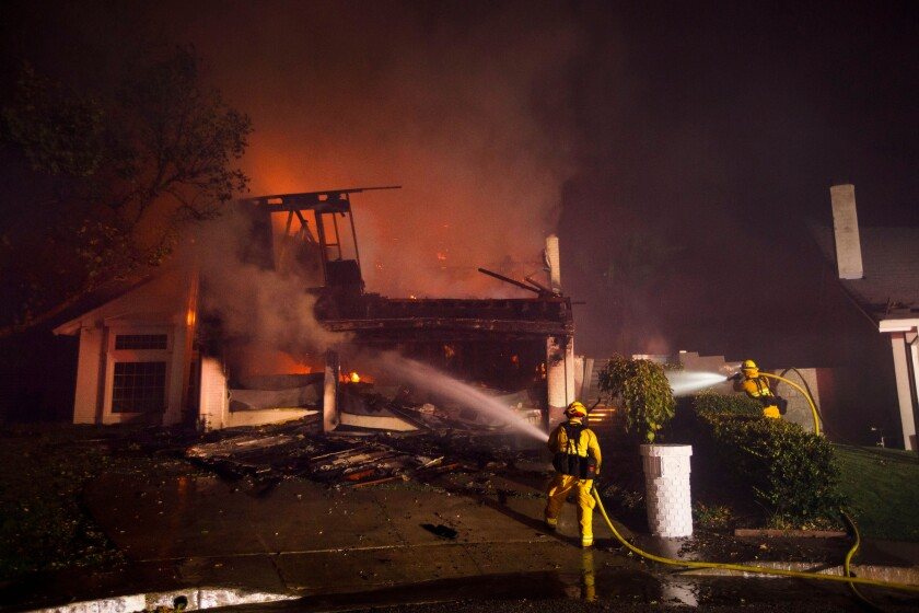 Firefighters work to contain a wildfire in the Porter Ranch neighborhood of Los Angeles.