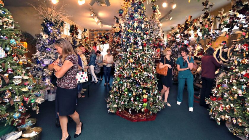 Customers inspect some of the many decorated Christmas trees on display at popular Canterbury Gardens on the first day of its Christmas sales season.