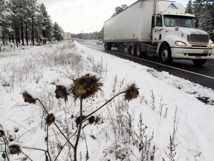 A truck drives down a slippery orad as snowy weather made travel slow in Flagstaff, Ariz., on Wednesday, Nov. 4, 2015, during the city's first snowfall of the season. Northern Arizona is getting an early taste of winter weather, with snow falling in Flagstaff and making roads and highways slippery.