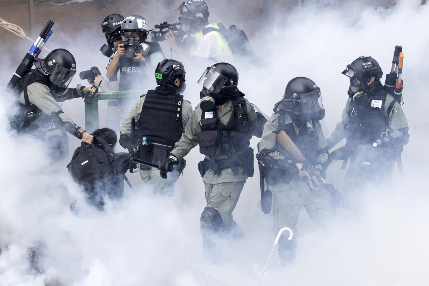 Police in riot gear move through a cloud of smoke as they detain a protestor at the Hong Kong Polytechnic University in Hong Kong, Monday, Nov. 18, 2019. Hong Kong police fought off protesters with tear gas and batons Monday as they tried to break through a police cordon that is trapping hundreds of them on a university campus. (AP Photo/Ng Han Guan)