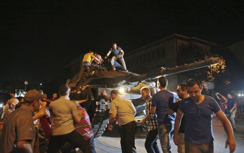 A tank moves into position as Turkish people attempt to stop them, in Ankara, Turkey, late Friday, July 15, 2016. Members of Turkey's armed forces said they had taken control of the country, but Turkish officials said the coup attempt had been repelled early Saturday morning in a night of violence, according to state-run media.(AP Photo/Burhan Ozbilici)