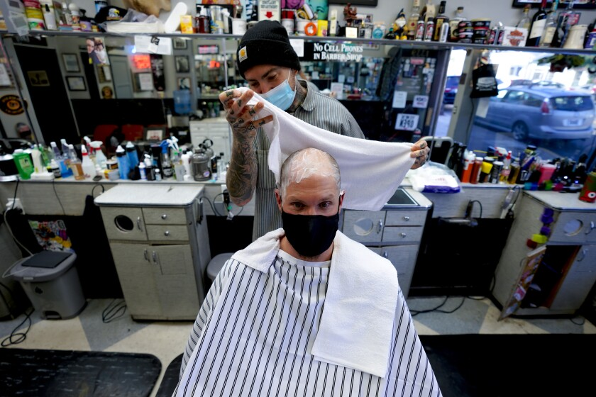Rob Hammer gets a head shave from Mikal Zack at Lefty's barbershop