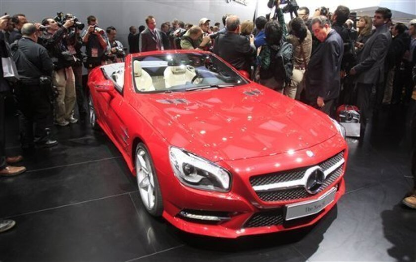 Journalists surround the 2013 Mercedes-Benz SL on the floor of the North American International Auto Show in Detroit, Monday, Jan. 9, 2012. (AP Photo/Carlos Osorio)