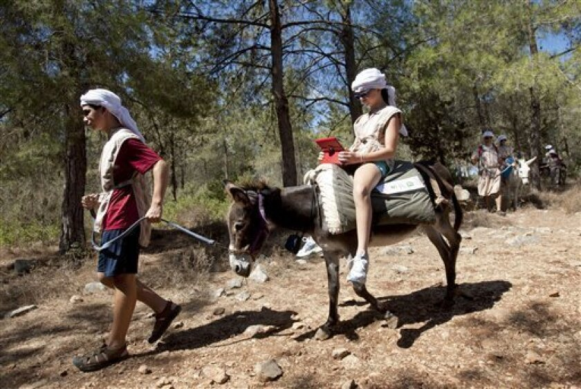 American tourist Ella uses an iPad while riding a Wi-Fi-outfitted donkey lead by her brother Aaron, in Kfar Kedem, a biblical reenactment park in the village of Hoshaya in the Galilee, northern Israel, Wednesday, Aug. 22, 2012. Visitors riding donkeys through the Old Testament landscape can now als