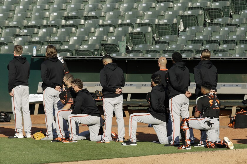 Some members of the San Francisco Giants kneel during the national anthem July 20 in Oakland.