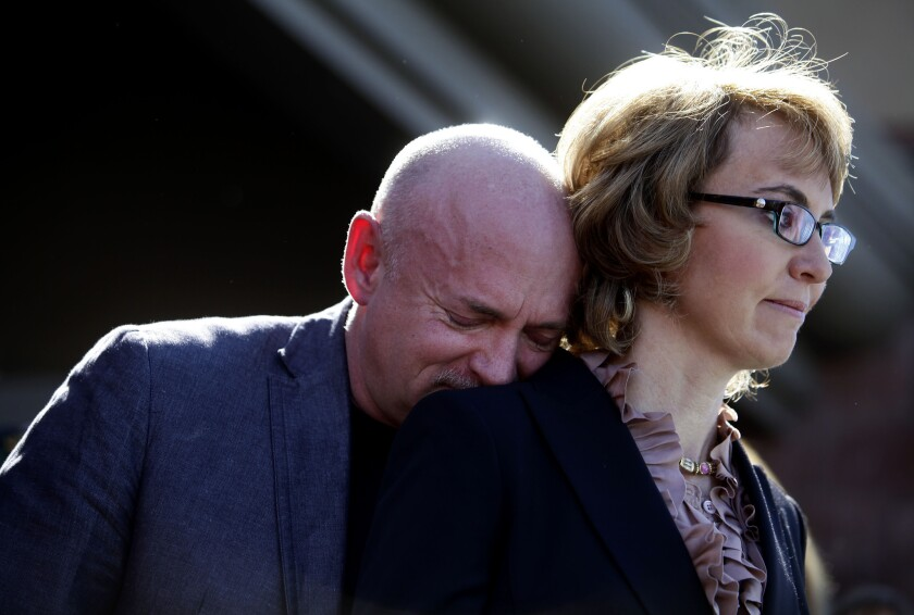 Mark Kelly leans his head on the shoulder of his wife and former U.S. Rep. Gabby Giffords as they attended a news conference last March asking Congress to pass stricter gun controls.