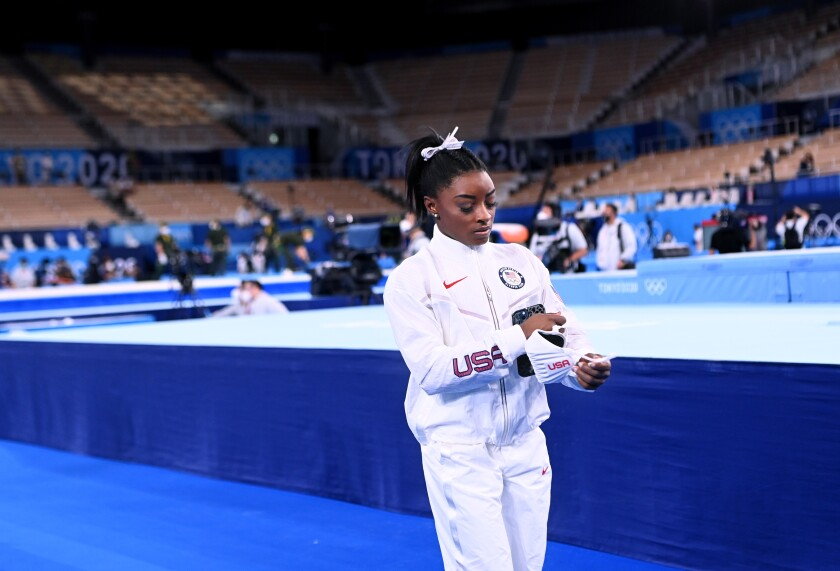 Simone Biles, in her Team USA warmup suit with media and empty stadium seats in the background.