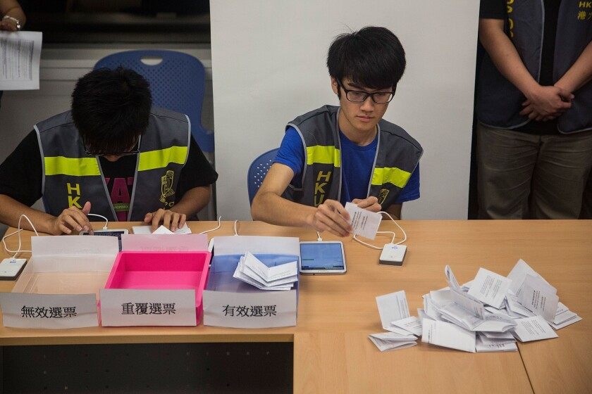 Ballot counting officers get to work in Hong Kong on Sunday after a 10-day pro-democracy vote was conducted online, via mobile phones and in person.