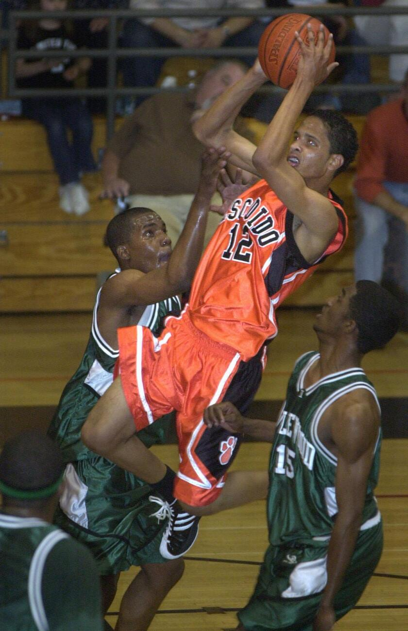 Escondido's Lorenzo Keeler goes up and over Inglewood's Gabriel Ognenekohud (left) and Chris Bell during a 2003 game.