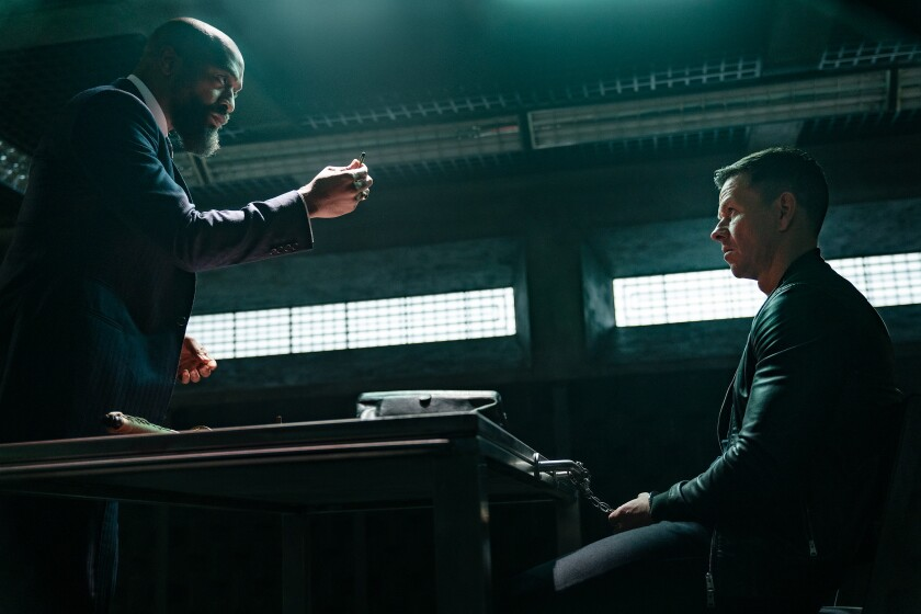 """Chiwetel Ejiofor stands in front of a seated Mark Wahlberg in the movie """"Infinite."""""""