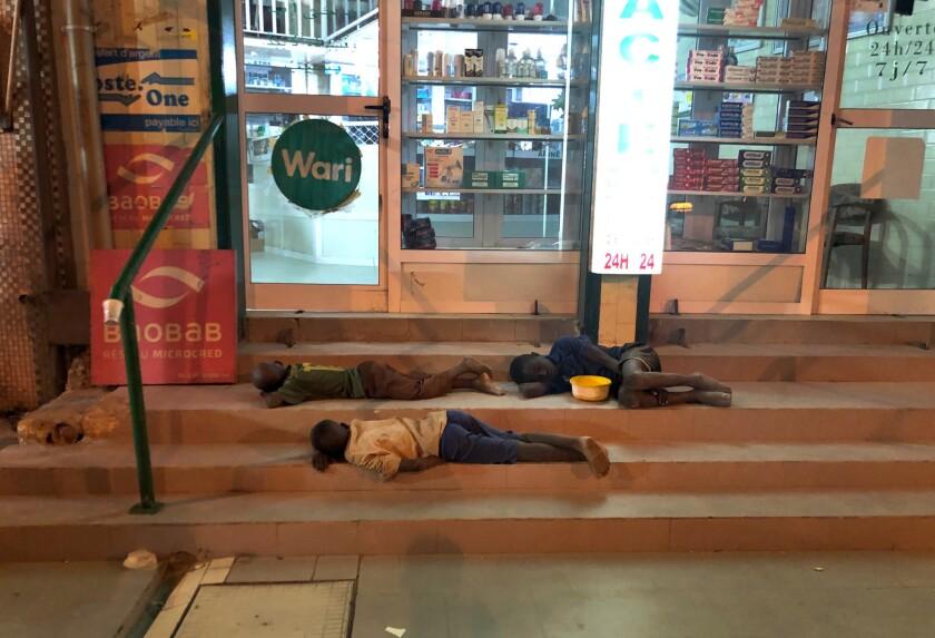 Talibes sleeping in a shopfront in Touba.