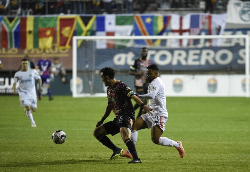 San Diego Loyal defender Elijah Martin (right) fights for the ball with Mobi Fehr of Las Vegas.