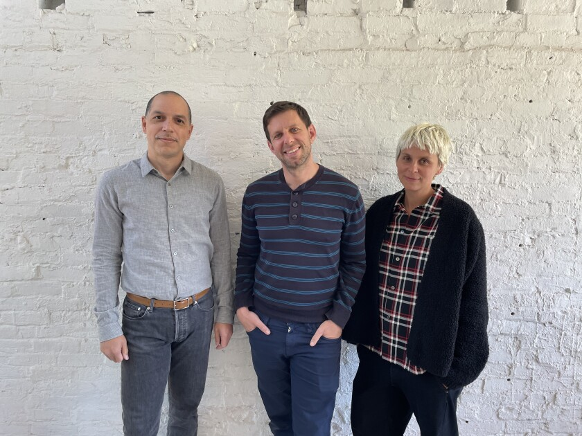 Three people stand in front of a wall.