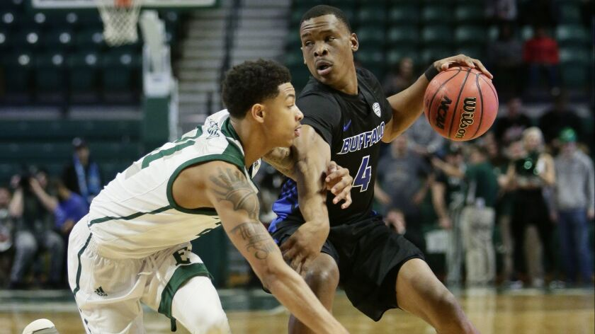 Buffalo guard Davonta Jordan tries to keep Eastern Michigan guard Kevin McAdoo from stealing the ball during the first half Friday.