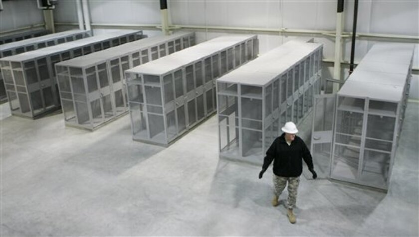 In this  Dec. 9, 2008 file photo, Col. John Dvoracek walks through new equipment storage space to the aviation brigade during a tour of new facilities at Fort Riley, Kan. Army officials in December  they were about halfway through a $1.7 billion construction boom that was started to handle the r