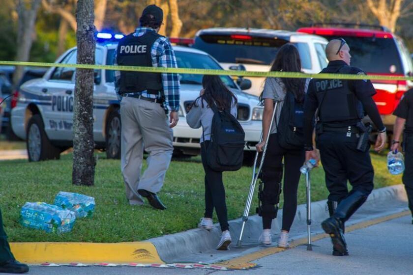 Miembros del personal de emergencias ayudan a varios estudiantes en el lugar del tiroteo registrado en la escuela secundaria Marjory Stoneman Douglas de la ciudad de Parkland, en el sureste de Florida (Estados Unidos). EFE